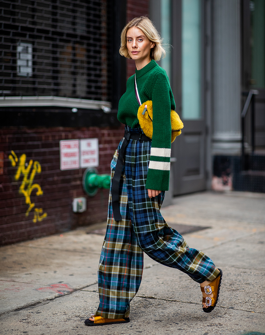 NEW YORK, NY - SEPTEMBER 12: Lisa Hahnbueck wearing checked pants Tibi, green knit Baum und Pferdgarten, yellow fake fur belt bag, sandals Roger Vivier is seen during New York Fashion Week Spring/Summer 2019 on September 12, 2018 in New York City. (Photo by Christian Vierig/Getty Images)
