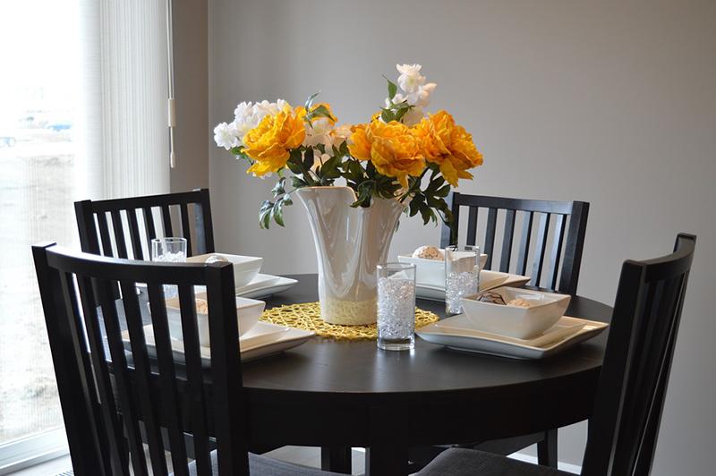Chiếc bàn ăn gỗ, được tô điểm bởi một chậu hoa tươi rực sắc, chắc chắn sẽ làm cho bữa ăn thêm ngon miệng