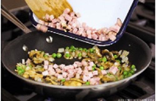 Bước 3: Cho một thìa dầu ăn, hành tây vào phi thơm, cho lần lượt đậu Hà Lan, nấm, thịt nguội vào đảo, nêm gia vị, hạt tiêu.