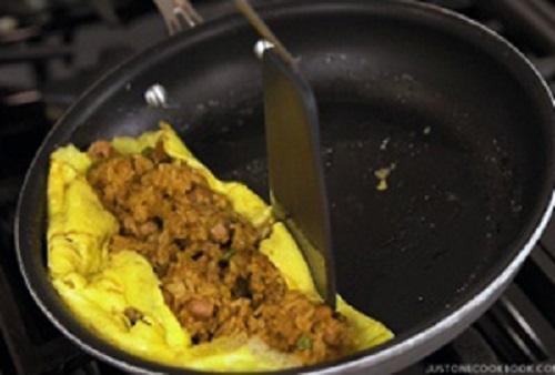 Bước 6: Cho cơm rang vào giữa, vun hai bên viền trứng, sau đó đổ ra đĩa, sao cho phần trứng ôm trọn lấy cơm. Cuối cùng cho cơm ra đĩa và đổ nước sốt lên trên.