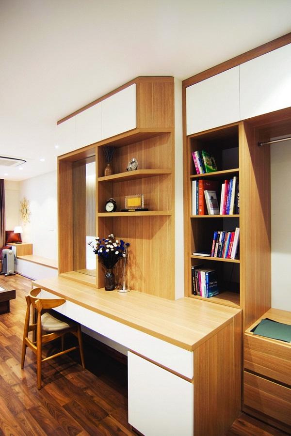 Mặt bằng căn hộ tương đối chặt chẽ và hợp lý, kiến trúc sư cơ bản giữ nguyên bố cục và cấu trúc. Tuy nhiên, để hoàn hảo hơn, kiến trúc sư đã điều chỉnh cửa vào phòng ngủ chính nhằm giúp phòng khách có một sự liền mạch xuyên suốt. Phòng khách và khu bếp ăn nằm giữa căn hộ, đóng vai trò không gian trung tâm theo nhiều nghĩa. Không gian này liên thông như thường thấy ở các căn hộ hiện đại, được xử lý với tông màu trầm ấm áp. Tuy vậy để hiện đại và cá tính, các mảng sáng được bố trí xen kẽ tạo nên sự tương phản ấn tượng. Phòng khách và bếp ăn mang một không khí ấm cúng, lịch lãm đúng như mong muốn của chủ nhân. Từ sảnh vào, một chiếc bàn  console được bố trí như sự chuyển tiếp mượt mà và đồng thời cũng là một điểm nhấn. Cửa vào phòng ngủ chính được sơn lại màu trắng như lẫn với bức tường. Các mảng trang trí tường, trần vừa phải, đem đến sự hấp dẫn nhưng không cầu kỳ, rườm rà.