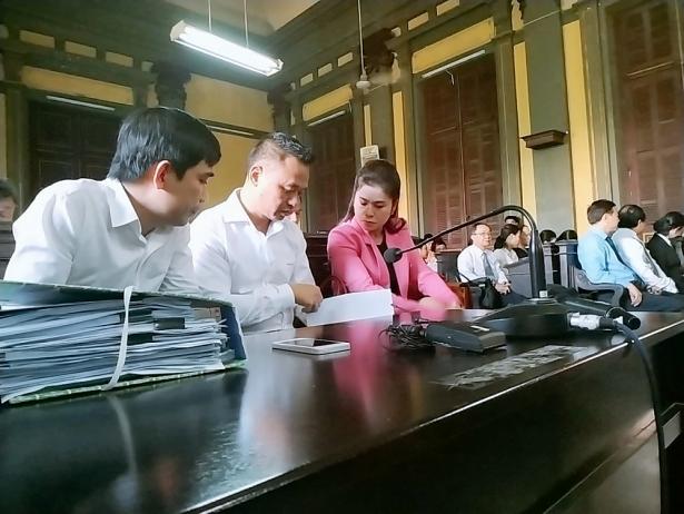 Bà Lê Hoàng Diệp Thảo xem tài liệu trong phiên tòa chiều 25/2. Ảnh: Minh Anh