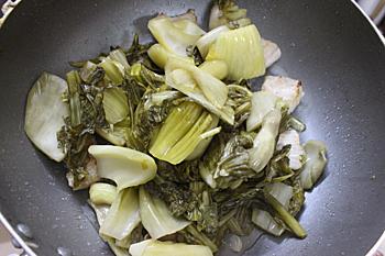 Bước 3: Phi thơm hành khô cho dưa chua vào xào, nêm gia vị và một bát nước. Dưa chua sôi cho cá chép, thịt ba chỉ vào om.