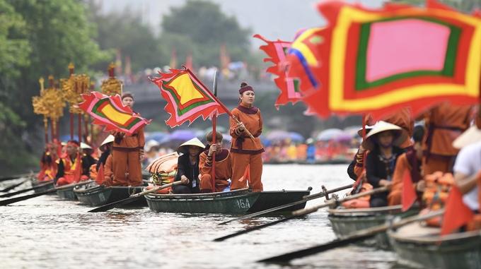 Đoàn cờ phướn nối đuôi trên sông trong hình ảnh nghĩa quân phất cờ hào hùng.