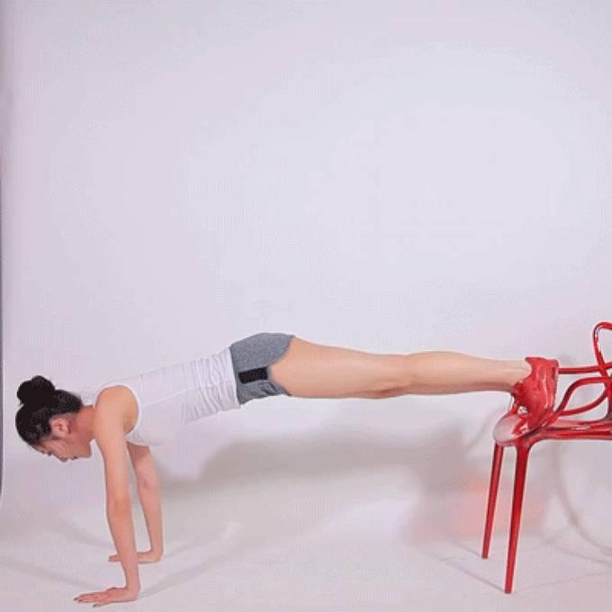 Chống đẩy với hai chân gác lên ghế, lần lượt đá chân lên cao tạo góc 90 độ. Thực hiện động tác mỗi chân 15 lần.