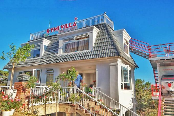 Căn biệt thự mang phong cách kiến trúc Pháp, mái ngói ghi, tường trắng. Cầu thang, ban công phía ngoài cũng sử dụng tone trắng - hồng làm chủ đạo, điểm xuyết nhiều chậu hoa hồng xinh xắn. Quán cà phê tận dụng phần mái rooftop còn phía dưới là phòng nghỉ cho khách.