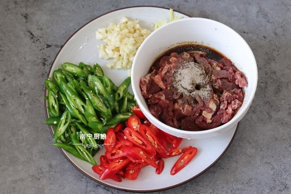 Thịt bò được rửa sạch, thái lát mỏng sau đó được trộn đều với nước tương, hạt tiêu và ướp trong 10 phút. Cùng với đó, ớt và gừng tỏi cũng được rửa sạch thái nhỏ.