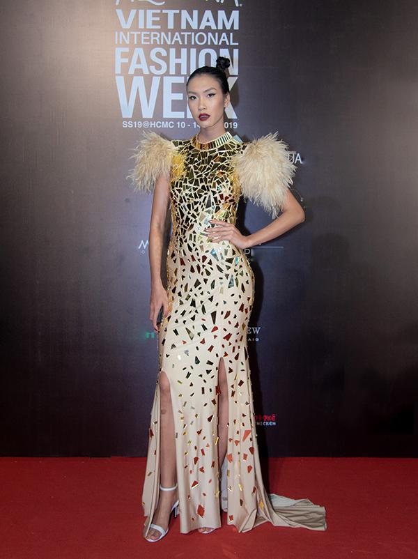 Nguyễn Oanh với váy dạ hội tham lam nhiều chi tiết như đính lông vũ, trang trí phụ liệu phản quang và đường cắt may chưa tinh tế.