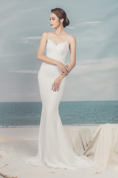 Váy hai dây đuôi cá có độ ôm sát, phô diễn đường cong gợi cảm của cô dâu. Độ xòe nhẹ từ đầu gối giúp nàng dễ di chuyển trong hội trường tiệc cưới.