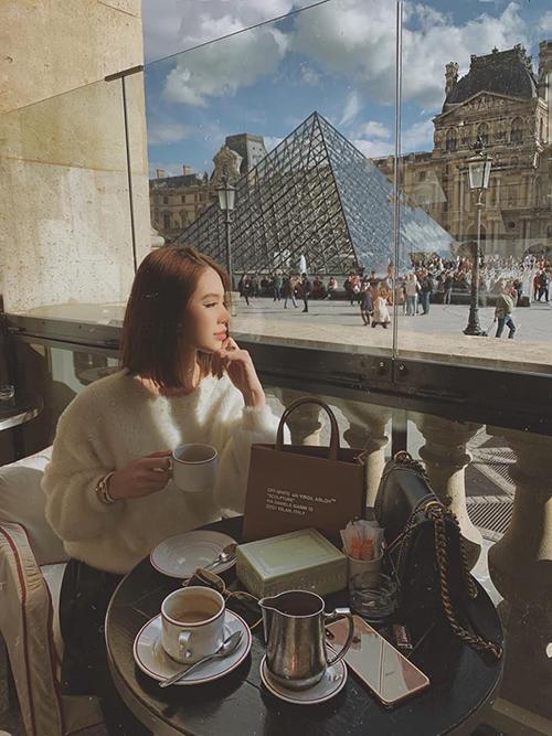 Jolie Nguyễn thảnh thơi uống cà phê trước bảo tàng Louvre (Pháp) trong chuyến du lịch Paris, không quên check in ở tháp Eiffel nổi tiếng.