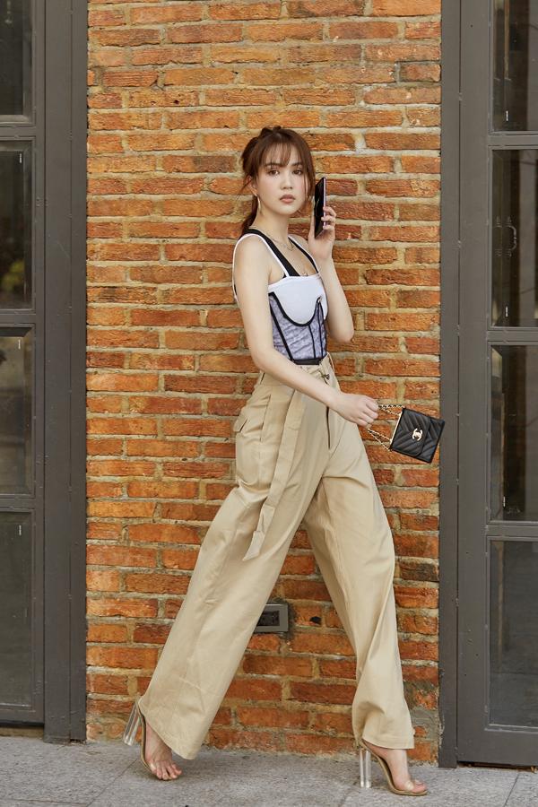 Cảm nhận nhanh nhậy về dòng chảy của xu hướng mới giúp Ngọc Trinh luôn thể hiện rõ tinh thần ăn mặc theo trend. Quần suông vải kaki tông cà phê sữa được cô phối cùng áo hai dây sexy.