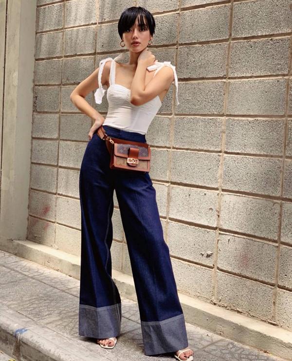 Khánh Linh The Face thể hiện sự cá tính và gợi cảm bằng việc chọn quần denim để mặc cùng áo hai dây biến tấu độc đáo. Phụ kiện túi đeo hông, sandal hợp mốt càng giúp hình ảnh của cô thu hút hơn.