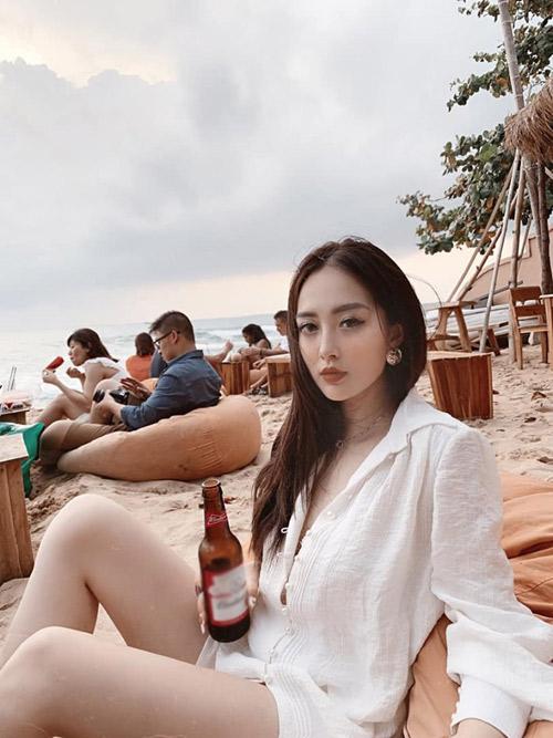 """Điểm đến tiếp theo được em họ Hương Tràm tư vấn là quán bar bên bờ biển Ocsen Beach bar - nơi ngắm hoàng hôn nổi tiếng ở Phú Quốc. """"Hãy tới đây, gọi đồ uống, ngắm trời, ngắm biển, một cảm giác thật 'chill'. Ở đây có lối bài trí bắt mắt và ấn tượng. Ghế ngồi là những bao hạt cát màu cam rất hợp cảnh, nhưng đặt ngay trên cát biển nên cảm giác hơi bẩn một chút. Mình ngồi chụp ảnh đủ mọi góc mà vẫn thấy chưa đủ vì cảnh đẹp mê mẩn, nằm ra ghế tận hưởng gió biển chẳng muốn về. Giá đồ uống tầm 70.000 - 100.000 đồng. Bên trong còn có cả bàn bi-a. Nói chung, nếu tới Phú Quốc thì bạn nên ghé qua nơi này thử một lần để cảm nhận"""", người đẹp sinh năm 1994 chia sẻ."""