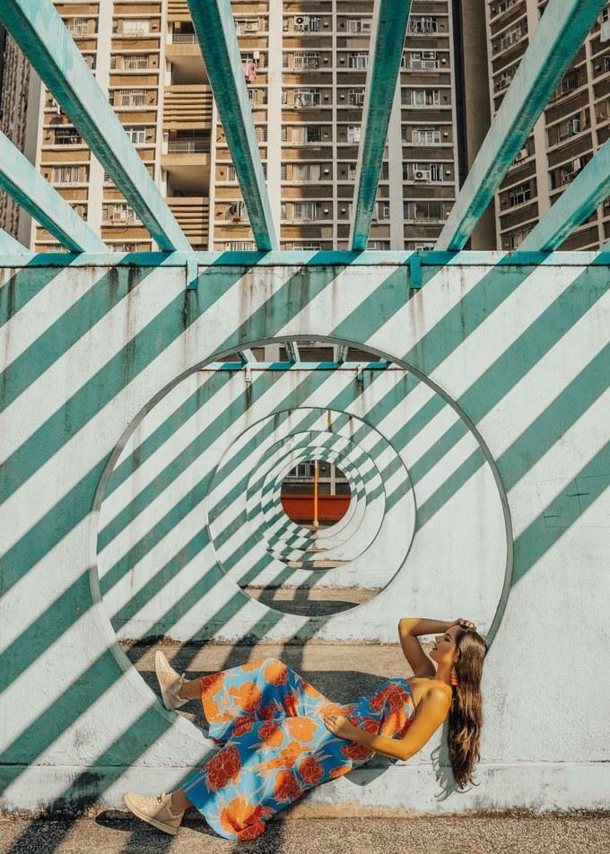 """Chung cư Lok Wah Bức ảnh """"siêu thực"""" này được chụp từ nóc bãi đậu xe của khu chung cư này. Những vòng tròn nối tiếp nhau, sơn màu xanh pastel. Khung cảnh càng nghệ thuật khi mặt trời lên in bóng của những thanh ngang phía trên, tạo nên hình ảnh rất nghệ thuật."""