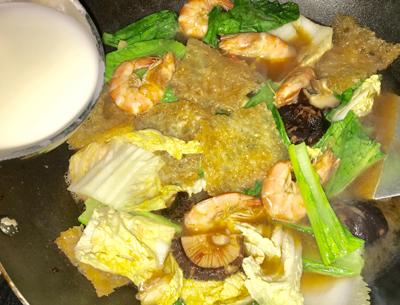 Bước 2: Phi thơm tỏi cho tôm vào xào, tôm chuyển màu, cho tiếp da heo, nấm, cho vào chảo một chén nước, dầu hào, nêm vừa miệng, tiếp đến cho cải vào đảo nhanh, rồi đổ từ từ phần bột năng vào để làm sệt.