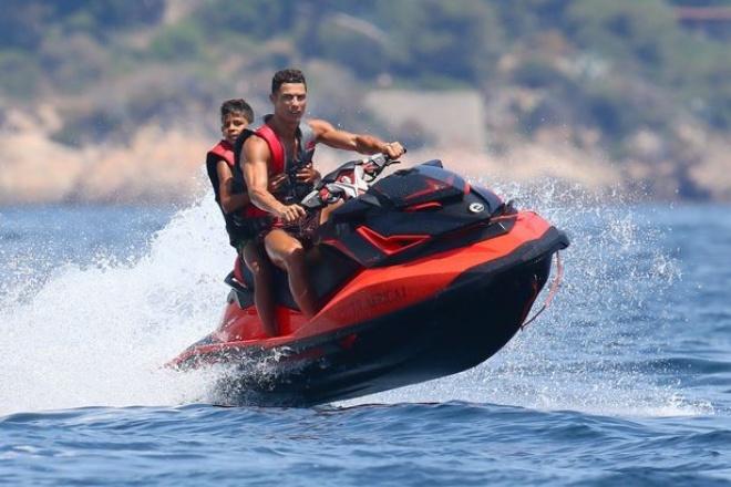 Cậu nhóc Cristiano Ronaldo Jr. ôm chặt trong khi bố lái môtô nước. Biển Saint Tropez là nơi lý tưởng để du khách trải nghiệm các trò lướt ván buồm, chèo thuyền cùng các môn thể thao dưới nước như trượt nước, lặn bình khí...