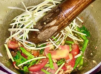 Bước 2: Cho đậu đũa, ớt, cà chua vào thố hoặc nồi, dùng chày đập. Cho vào thố 2 muỗng đường, 2 muỗng nước mắm, 3 muỗng cốt chanh, thêm lạc vào vừa dầm vừa trộn. Nếm thử vị vừa chưa rồi cho tiếp phần đu đủ, ngò gai, phần nước trộn ba khía vào, trộn cho thấm đều.