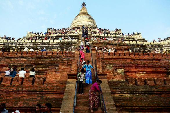 Du khách chờ ngắm hoàng hôn từ đỉnh chùa Shwesandaw ở Bagan. Ngắm hoàng hôn hay bình minh trên nóc các ngôi chùa là một trong những điều thu hút du khách nhưng có hại cho các ngôi chùa - Ảnh: REUTERS