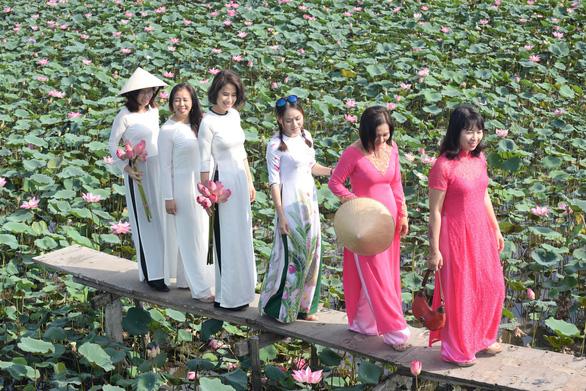 Áo dài là trang phục chính của hầu hết khách ở vườn sen Q.9 - Ảnh: T.T.D