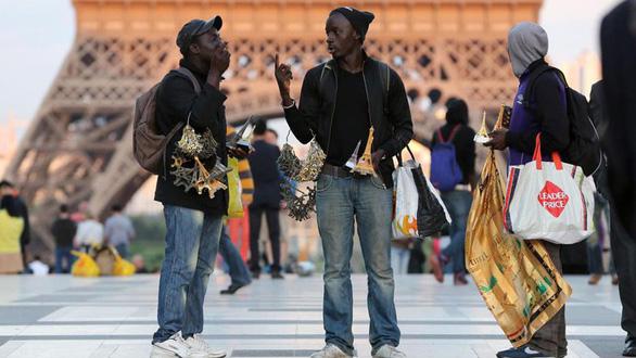 Hai thanh niên châu Phi đang bán mô hình tháp Eiffel dưới chân tháp Eiffel - Ảnh: LE PARISIEN