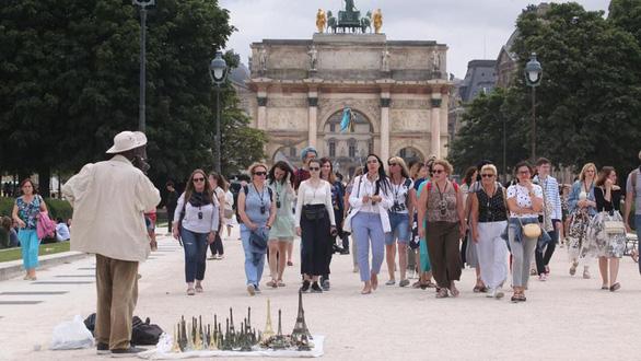 Hàng lưu niệm mô hình tháp Eiffel được bày bán bất hợp pháp khắp nơi tại những điểm tham quan du lịch ở thủ đô Paris. Đây là đường dây kinh doanh lậu thuế do những người nhập cư không giấy tờ đứng ra tổ chức một cách rất bài bản - Ảnh: LP/Olivier Boitet