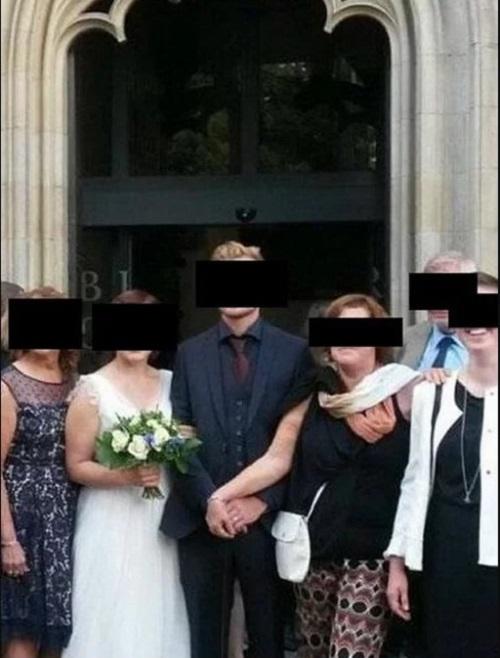 Mẹ chú rể mặc áo đen, giữ chặt hai tay của con trai không buông.