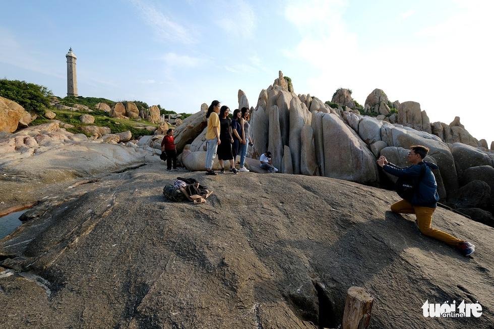 Du khách chụp ảnh lưu niệm với ngọn hải đăng Kê Gà trên đảo - Ảnh: NAM TRẦN
