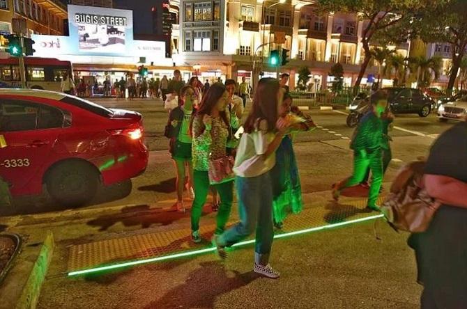 """Ngày nay, điện thoại trở nên rất phổ biến. Không khó để bắt gặp những người đang đi bộ trên đường nhưng mặt vẫn """"cắm"""" vào thiết bị trên tay. Để đảm bảo an toàn cho những người này, chính phủ Singapore cho lắp một hệ thống dải phân cách chìm dưới đất để tránh trơn trượt. Hệ thống này còn có đèn phát sáng, để dù đang dùng điện thoại, người đi bộ vẫn được cảnh báo đang bước xuống lòng đường, cần chú ý an toàn."""