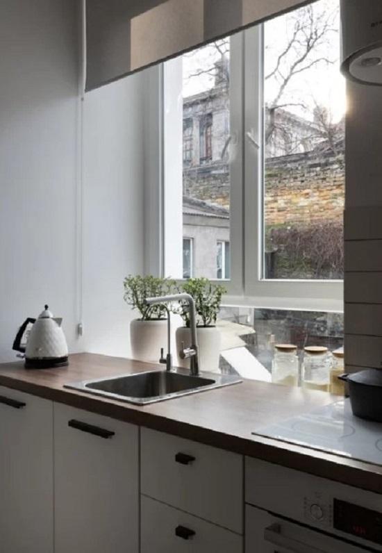 Bậu cửa sổ nằm sau bàn bếp là nơi đặt lọ gia vị và trồng các cây thảo mộc.