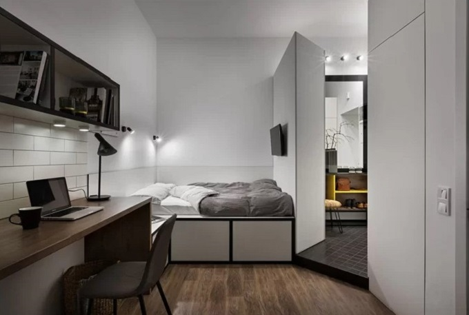 Giường ngủ ở bên trên và ngăn đựng đồ bên dưới để tối ưu hóa không gian trong căn phòng. Phía trên tường có gắn đèn ngủ và TV.