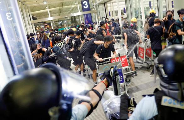 Cảnh sát Hong Kong đụng độ với người biểu tình ở sân bay Hong Kong tối 13-8 - Ảnh: REUTERS
