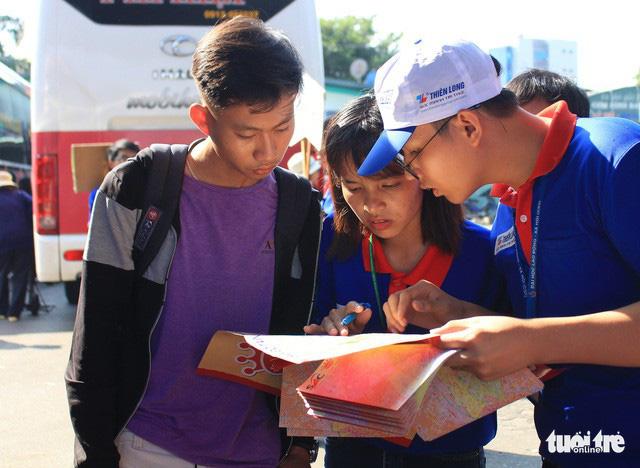 Bạn Trần Đức Quyền - tân sinh viên trường ĐH Công Nghiệp TP.HCM, được các tình nguyện viên hướng dẫn tìm đường đến nhà trọ - Ảnh: THANH YẾN