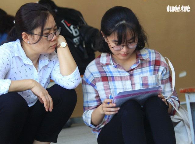 Mẹ cũng lo lắng cho con gái khi điền thông tin vào hồ sơ nhập học - Ảnh: THANH YẾN