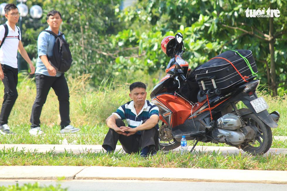 Ông Lê Văn Nam (đến từ Đắk Lắk) ngồi đợi con trai làm thủ tục nhập học tại trường ĐH Bách Khoa - Ảnh: THANH YẾN