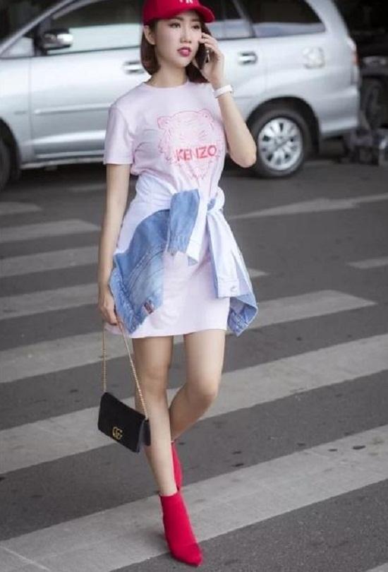 Người đẹp trông trẻ trung như gái 18 với váy ngắn gam hồng, áo khoác jeans buộc ngang hông và mũ lưỡi trai.