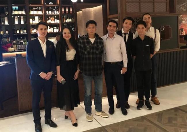 Tạ Đình Phong (áo kẻ, đứng giữa) tiếp khách tại tiệm của anh.