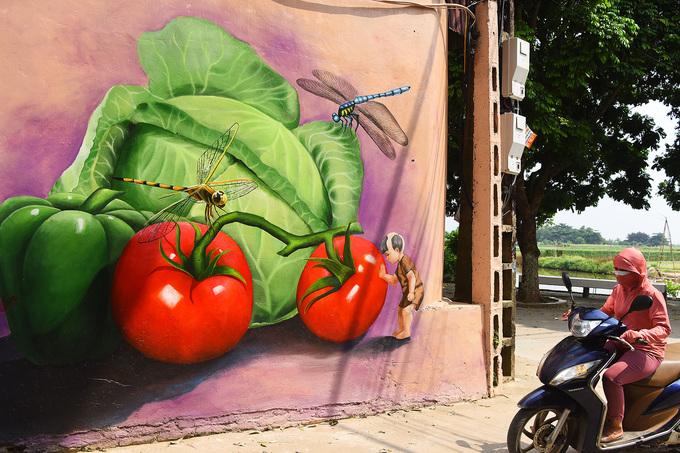 Các sản phẩm nông nghiệp như rau, củ quả gắn liền với công việc hàng ngày của người dân địa phương được thể hiện sinh động trên tường.