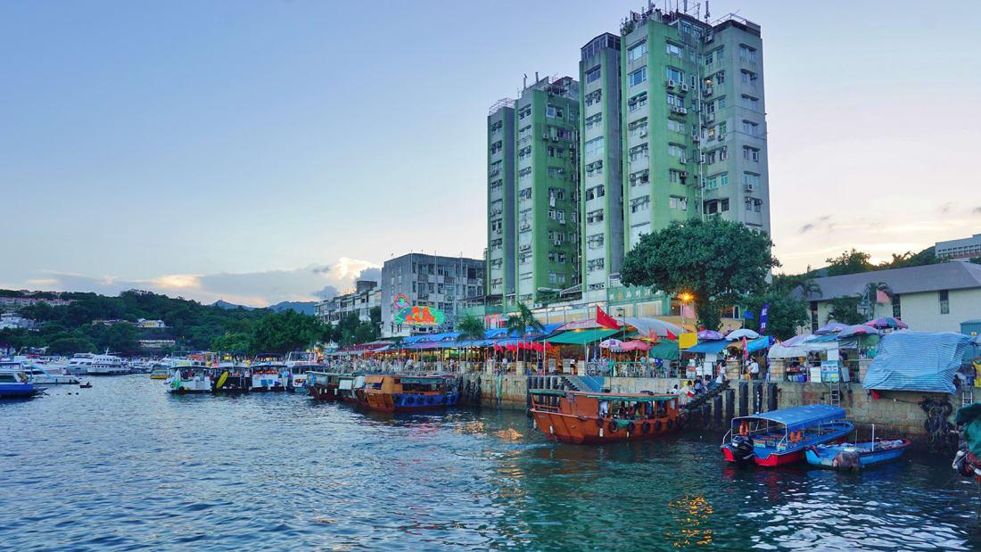 """Trái với khung cảnh nhà cao tầng và giao thông dày đặc, Sai Kung được xem như """"lá phổi xanh"""" của Hong Kong, có núi nhấp nhô, hòn đảo xanh tươi và ngôi làng nhỏ ven biển. Không còn sự hối hả, mà chỉ có những chiếc thuyền câu cá đầy màu sắc neo đậu bên bến cảng, tiệm bánh bình dân và nhịp sống nhàn nhã khiến du khách cảm thấy thoải mái khi đến đây."""