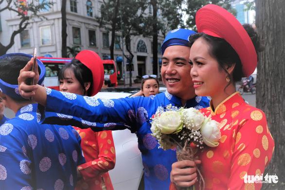 Cô dâu Nguyễn Thị Mỹ Loan (27 tuổi) và chú rể Nguyễn Hoàng Minh (29 tuổi) hào hứng chụp selfie trước khi lên xe hoa - Ảnh: VŨ THỦY
