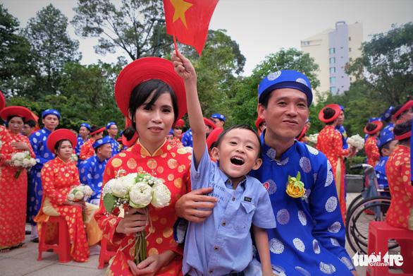 Cậu bé Phúc Vinh (5 tuổi) cùng ba và mẹ là công nhân công ty Year2000 ở lễ cưới - Ảnh: VŨ THỦY
