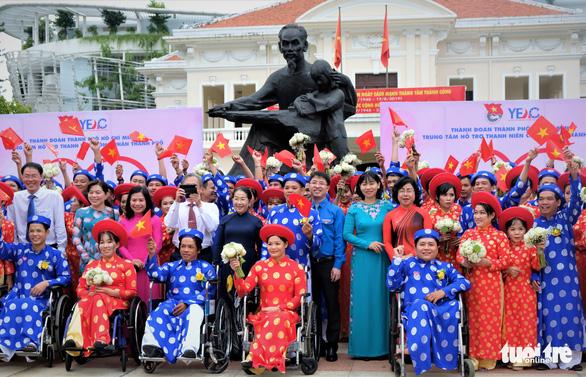Các đôi uyên ương cùng ghi lại khoảnh khắc kỷ niệm cùng với lãnh đạo TP và Thành đoàn TP.HCM dưới chân tượng đài Bác Hồ với thiếu nhi tại Nhà văn hóa thiếu nhi TP - Ảnh: VŨ THỦY