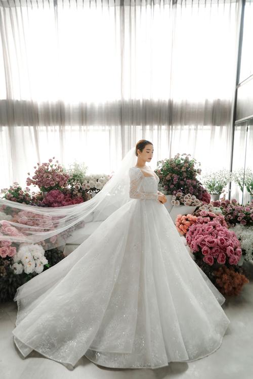 Váy mang đậm phong cách hoàng gia nhờ thiết kế tay bồng, cổ vuông thêu ren cầu kỳ.