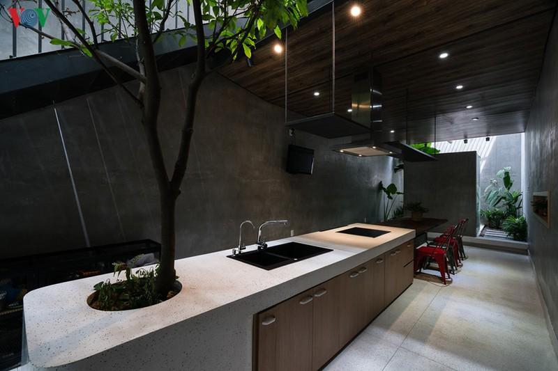 Gian bếp không tổ chức hệ thống tủ bếp sát tường như thông thường mà thiết kế thành đảo bếp nằm giữa nhà, như một điểm nhấn. Bàn ăn nằm phía trong gần sân sau.