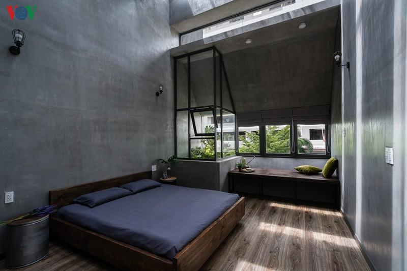Phòng ngủ chính nằm trên tầng, phía trước nhà, với một ô kính chứa bồn cây xanh. Sàn lát gỗ để đảm bảo tiện nghi và vệ sinh, nhưng tường vẫn nhất quán với màu xám xi măng.