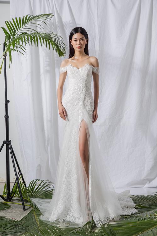 2. Váy trễ vai xẻ tà  Trễ vai là kiểu dáng váy giúp cân đối thân hình của cô dâu vai xuôi hoặc có bắp tay kém thon. Phần họa tiết ren dày dặn trải dài dọc thân xóa bớt nhược điểm vóc dáng gày gò của cô dâu.