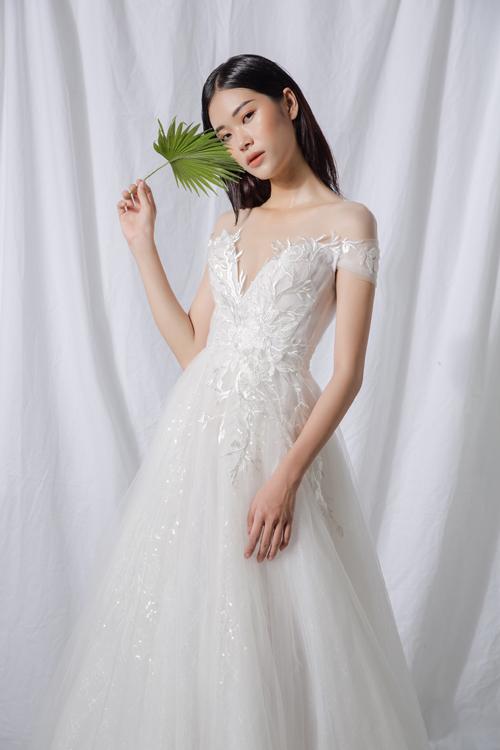 4. Váy cổ V trễ vai  Mẫu đầm xòe nhẹ lấy cảm hứng của váy công chúa phương Tây là lựa chọn phổ biến của cô dâu. NTK thêu đính ren ở phần thân trên tới ngang hông để tạo điểm níu giữ ánh nhìn.