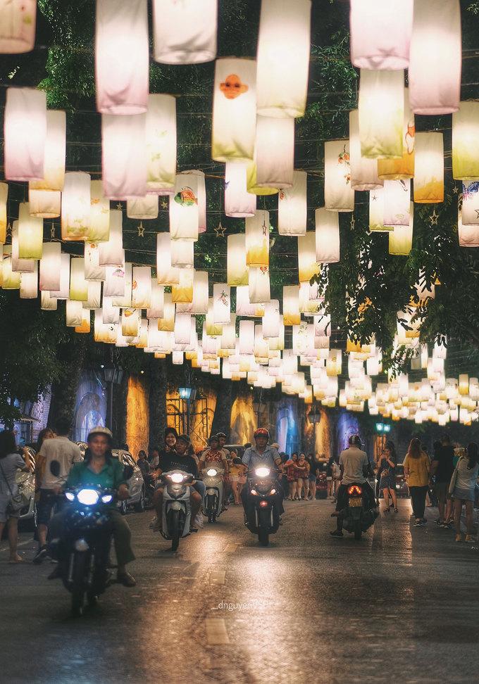 """Đêm xuống, cả đoạn đường bừng sáng dưới ánh đèn lấp lánh. Rất nhiều bạn trẻ, du khách đến đây chụp hình. """"Mình đến Hà Nội nhiều lần nhưng đây là lần đầu được đi dạo dưới hàng nghìn chiếc đèn lồng đẹp như cổ tích thế này"""", Ái Duyên, nữ du khách đến từ Đà Nẵng nói."""