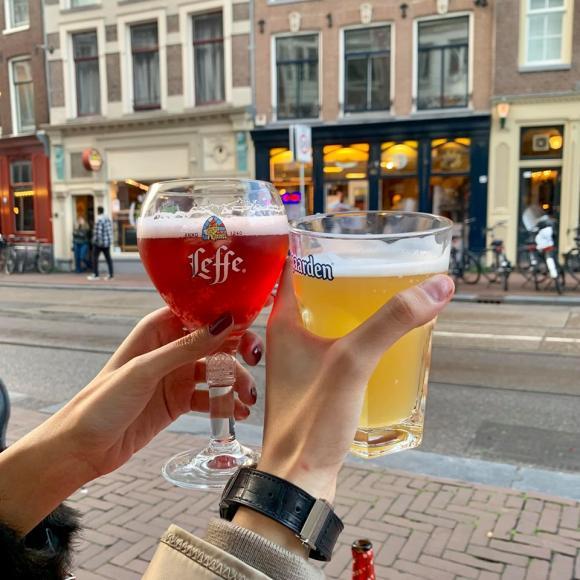 """Kỳ Duyên, Minh Triệu uống bia ngắm đường phố. Cô khuyên mọi người: """"Bia ở đây nặng lắm nên uống từ từ thôi không lại say như mình, thấy ngon quá làm 1 hớp dài thế là lừ đừ luôn""""."""