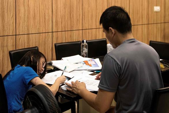 Một học sinh học bài với gia sư tại nhà em - Ảnh: AFP