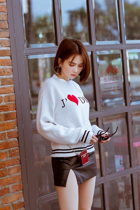 Phong cách thu đông sexy và trẻ trung với áo hoodie của Dior, chân váy da siêu ngắn và túi mini bé xinh của Roger Vivier.